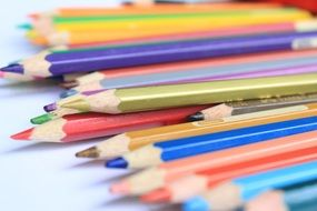 colored pencils of bright colors on a white background