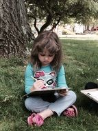 little girl doing homework under a tree