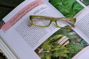 green glasses on the book