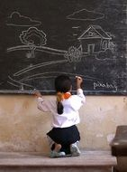 girl draws a house and a tree on the board