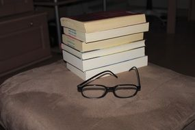 stack of books and black reading glasses