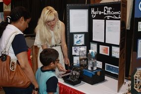 student with parents at a science fair