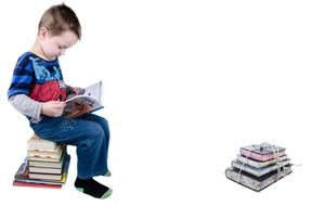 boy sitting on books and reading book