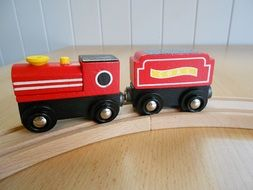 children's wooden red train on wooden rails
