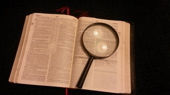 opened bible and magnifying glass
