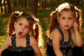 twin sisters with blue eyes in identical dresses