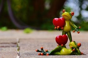 two ceramic figures of frogs with hearts