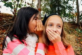 girls whispering and smiling in park