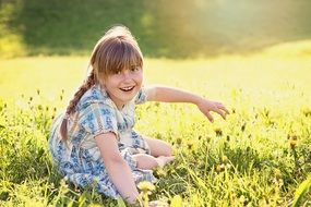 blond girl sitting on the meadow