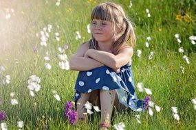cute blond girl sitting on the meadow