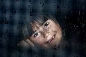 The child\'s face through the window glass and raindrops