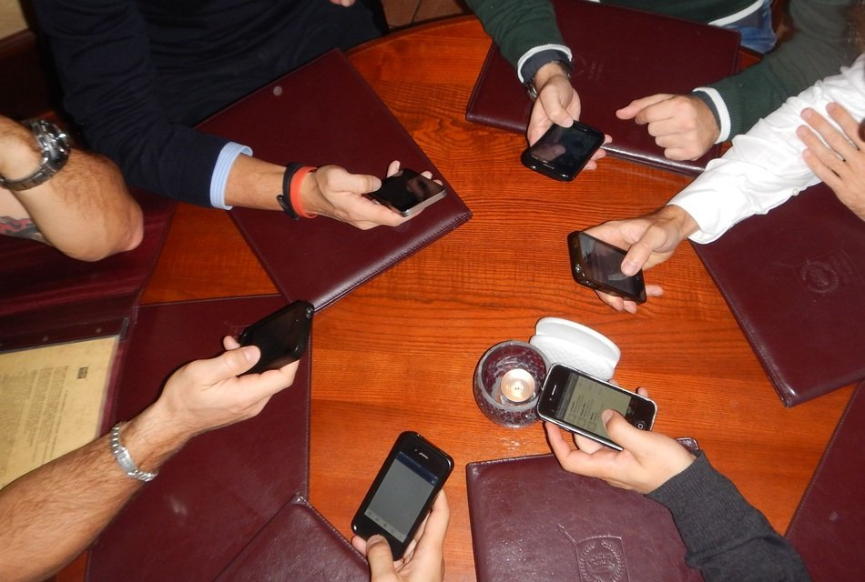 people with smartphones at the round table