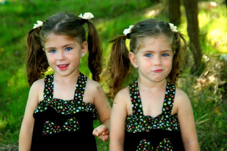 two sisters twins with the same hairstyles in identical dresses
