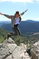 Hipster girl is jumping on top of a mountain