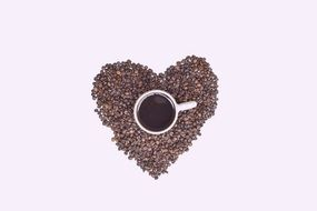 coffee cup standing on coffe beans in shape of heart