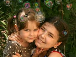 the sisters hugging on the background of soap bubbles