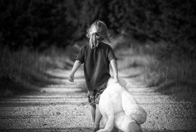 girl drags a white teddy bear along a rural road