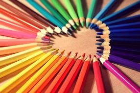 pencils of different colors laid out in the shape of a heart
