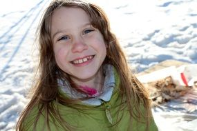 photo portrait of a smiling girl on a background of a winter landscape