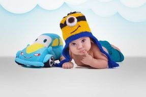 baby in minion hat and toy machine