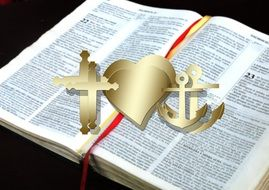bible and images of cross , heart and anchor