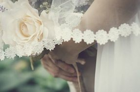 white rose in the hands of the bride