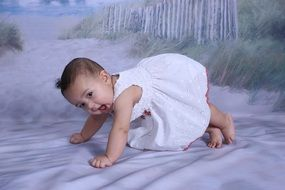 baby in a white dress on white sand