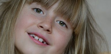beautiful face of a little girl with freckles