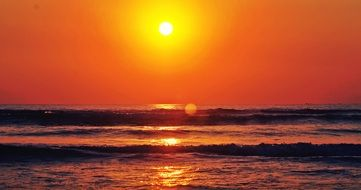 bright yellow sun over the ocean in the early morning