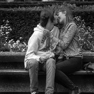 young people kiss on the bench