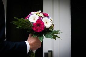 bouquet in the hands of the groom