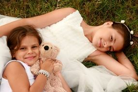 two happy girls with a teddy bear in a meadow