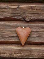 metal figurine of a heart on a wooden wall