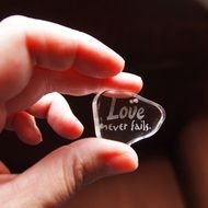 glass with letters in hand, love never fails