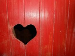 a hole in the red door in the shape of a heart
