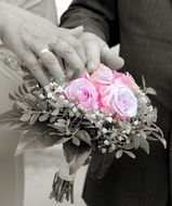 hands of the newlyweds on the wedding bouquet