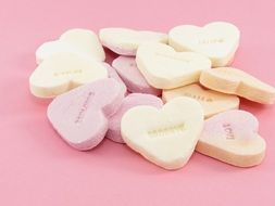 sweets in the form of heart on a pink background