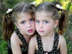 Two sisters twins in sundresses