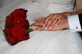 bride and groom hands on wedding bouquet