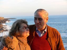 photo of an elderly couple on the background of the sea in autumn