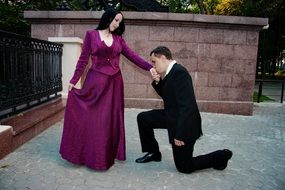 a man kneels in front of a woman and kisses her hand