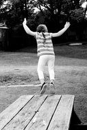 girl is jumping from a wooden bench