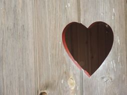 heart form hole in wooden panel