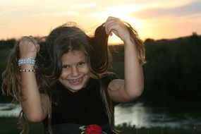 funny child girl with long hair at sunset