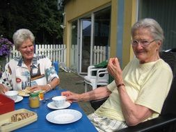 two senior women eating at table