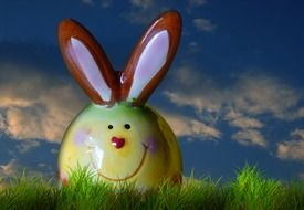funny easter bunny figurine on green grass