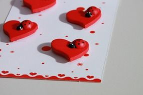 decorating a card with hearts and ladybirds