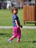 little girl in pink shorts in the park