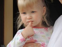 girl with blue eyes holds a finger in her mouth