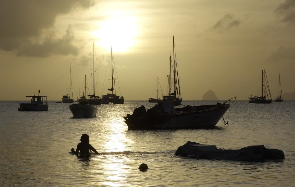 sunset seascape with boats and swimmer